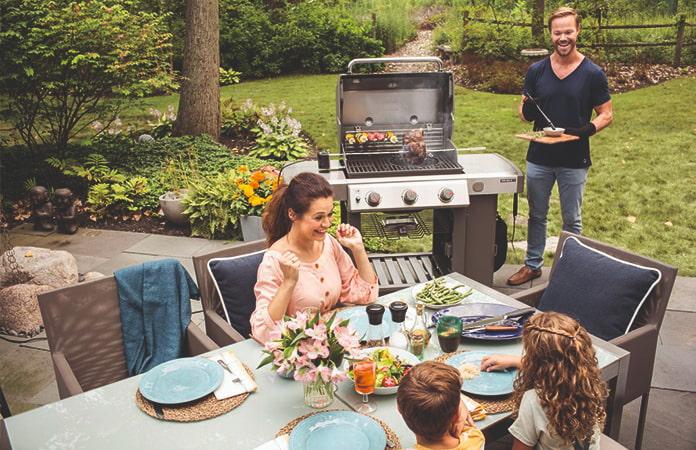 Perhe on grillaamassa vehreällä pihalla. Nauravainen mies kantaa kaasugrilliltä ruokaa pöytään, jossa innostunut nainen, pikkutyttö ja pikkupoika ovat kerääntyneet katetun pöydän ääreen.