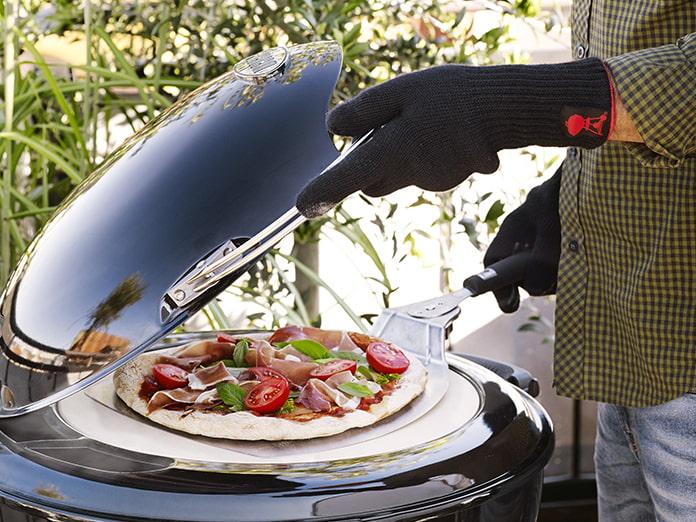 Mieshenkilö avaa grillihanskoilla hiiligrillin kannen ja asettaa pizzan paistumaan pizzalapiolla pizzakivelle.