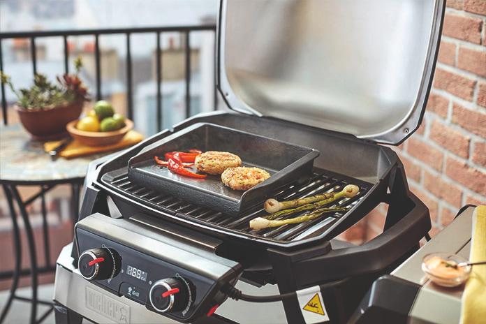 Parvekeella on sähkögrilli, jossa grillautuu herkullisia kasviksia ja kasvisruokaa. Grillin takana on parvekepöytä, jolla on hedelmävati.