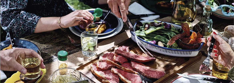 Rustiikkinen ruokapöykä on katettu täyteen erilaisia herkkuja. Joukko ihmisiä on kerääntynyt syömään pöydän ääreen, mutta ainoastaan heidän aterimia ja juomalaseja pitelevät kätensä näkyvät kuvassa.